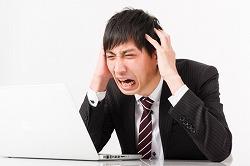 海外で英語が話せずに頭を抱える一人の男性の画像 写真